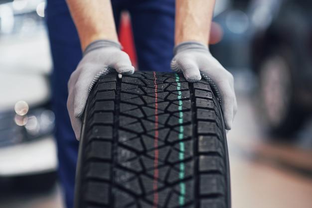 Closeup de mãos mecânicas empurrando um pneu preto na oficina