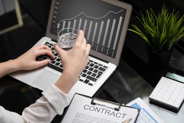 Closeup de mãos segurando um copo de água e se familiarizando com o contrato