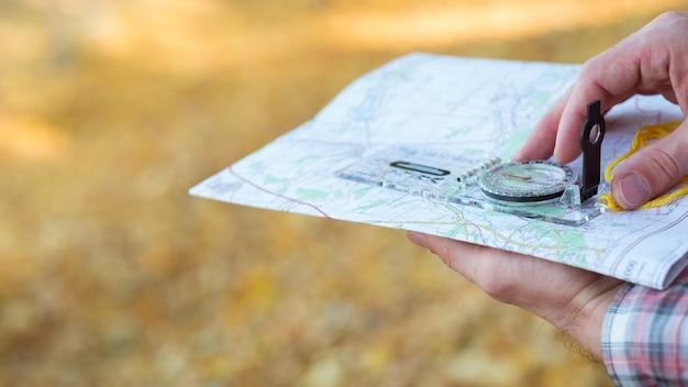 Closeup de mãos segurando uma bússola e um mapa