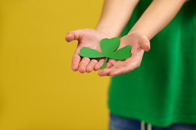 Closeup de mãos segurando uma folha de trevo verde na superfície de um menino de pé na superfície amarela com espaço de cópia