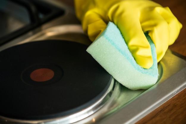 Closeup de mãos usando luvas, limpando o conceito de tarefas domésticas de fogão