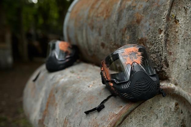 Closeup de máscara de proteção de paintball, ninguém, playground na floresta no fundo. esporte extremo ao ar livre, arma pneumática e balas de tinta, conceito de jogo de equipe militar