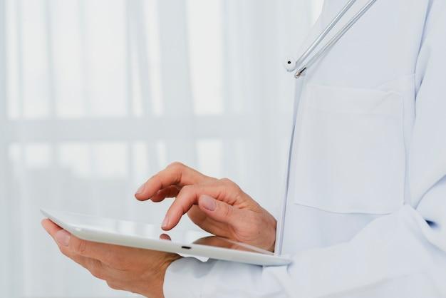 Closeup de médico usando tablet