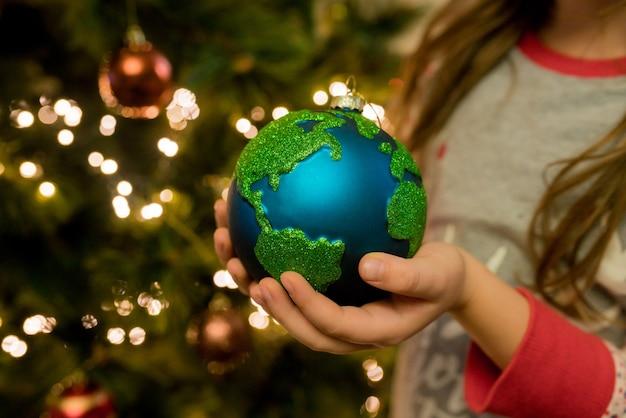 Closeup de menina pendurada enfeite de enfeite de decoração de bugiganga de vidro de natal no natal