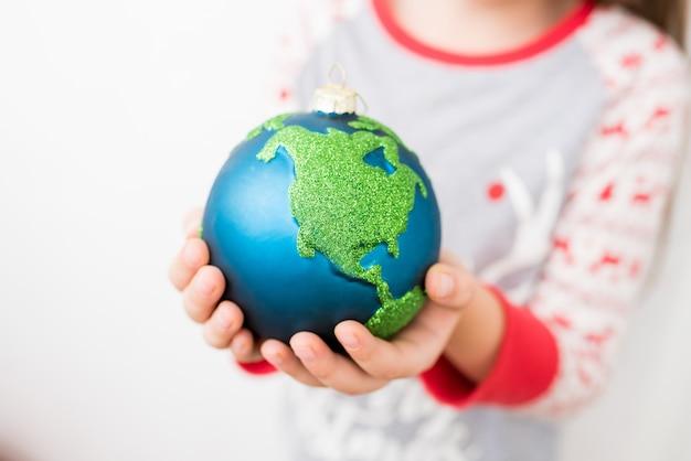 Closeup de menina segurando nas mãos natal bugiganga decoração ornamento globo planeta terra