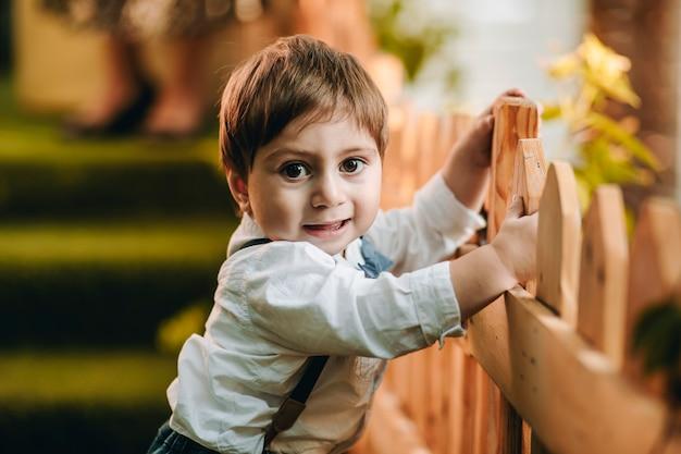 Closeup de menino alegre no parquinho segurando em uma cerca de madeira