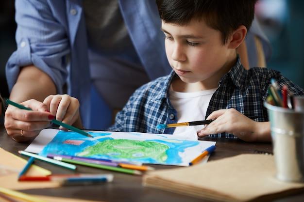 Closeup de menino desenhando fotos com a mãe