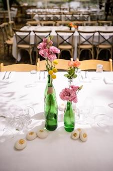 Closeup de mesas de casamento decoradas, com guardanapo de flores e talheres