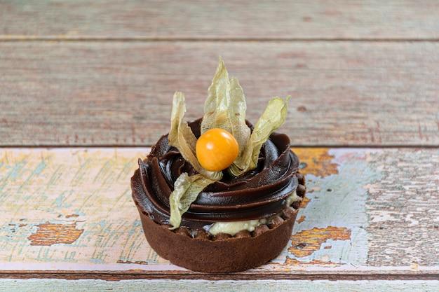 Closeup de mini torta com creme de mascarpone e ganache de chocolate, decorado com physalis.