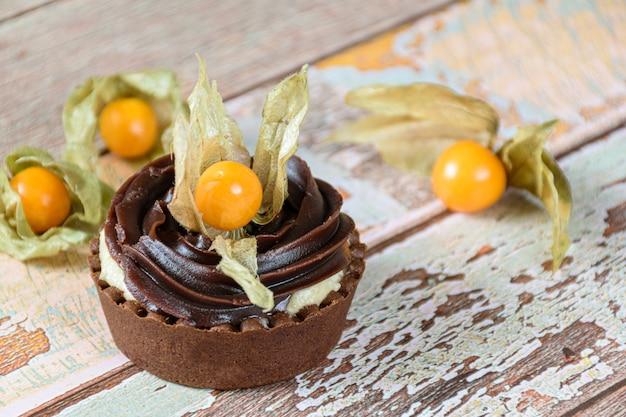 Closeup de mini torta com creme de mascarpone e ganache de chocolate, decorado e rodeado com physalis.