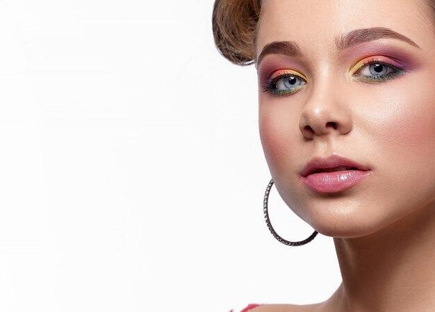 Closeup de modelo com maquiagem colorida e sombras brilhantes