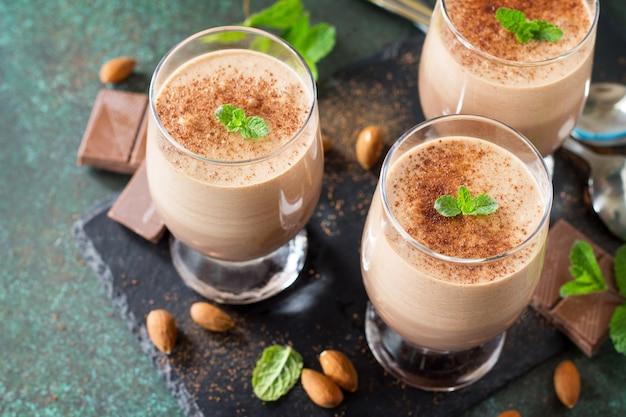 Closeup de mousse de chocolate com hortelã em copos de dose em um fundo de pedra ou ardósia