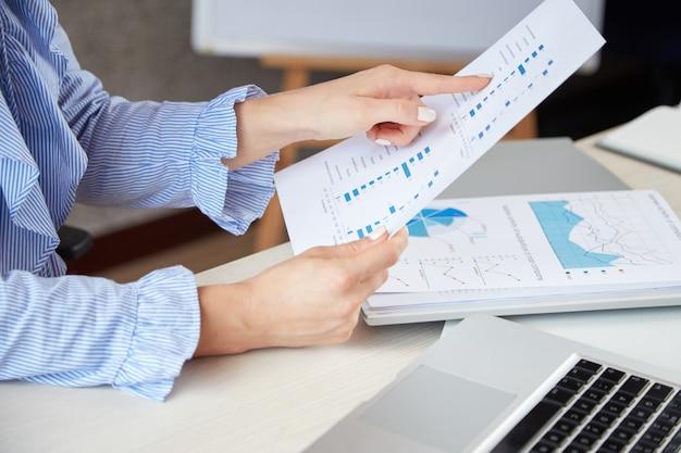 Closeup de mulher anônima segurando uma folha de papel e apontando para diagramas nele