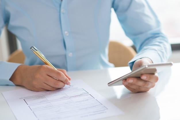 Closeup, de, mulher, assinando documento, e, segurando, smartphone