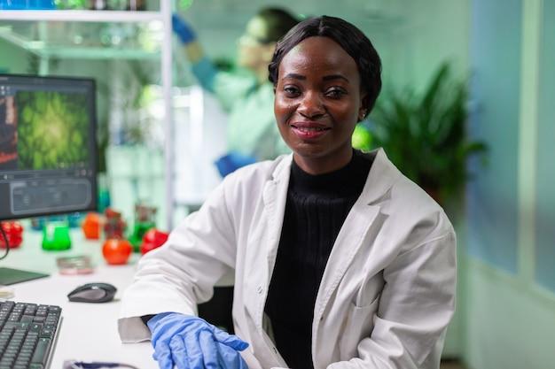 Closeup de mulher bióloga africana olhando para a câmera enquanto trabalhava no laboratório biológico