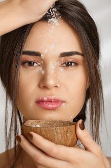 Closeup de mulher bonita, derramando esfoliação com sal