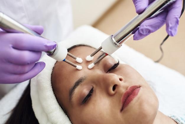 Closeup de mulher bonita recebendo tratamento facial com microcorrente de terapeuta no salão de beleza