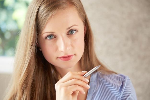 Closeup de mulher caucasiana, olhando para a câmera, segurando a caneta