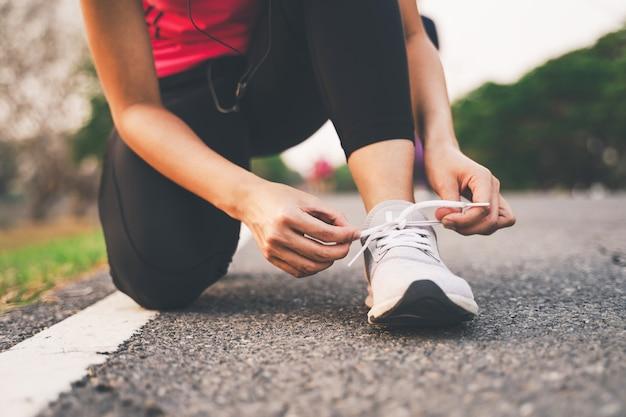 Closeup de mulher de fitness amarrar cadarços de sapato no parque durante o pôr do sol