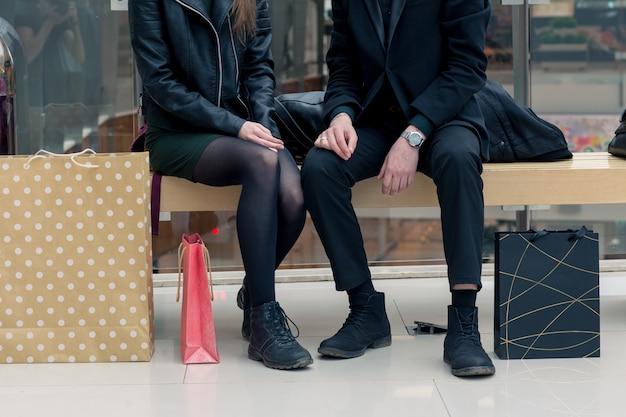 Closeup de mulher e homem no banco com sacolas coloridas
