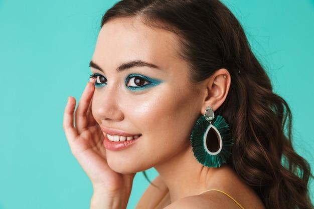 Closeup de mulher elegante usando moda maquiagem e brincos, sorrindo e olhando de lado
