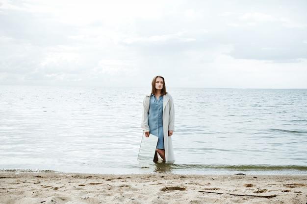Closeup de mulher em pé em uma costa no vestido azul, segurando um espelho com água refletindo sobre ele
