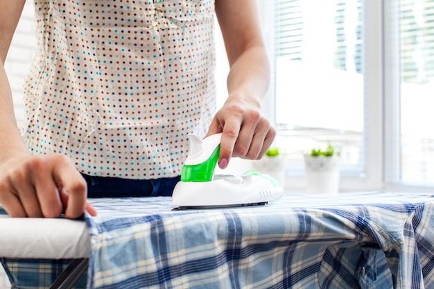 Closeup, de, mulher, ironing roupas, ligado, tábua ironing