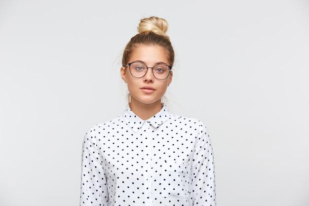 Closeup de mulher jovem e bonita séria com coque, usando camisa de bolinhas e óculos