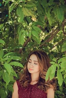 Closeup de mulher na floresta curtindo a natureza com os olhos fechados