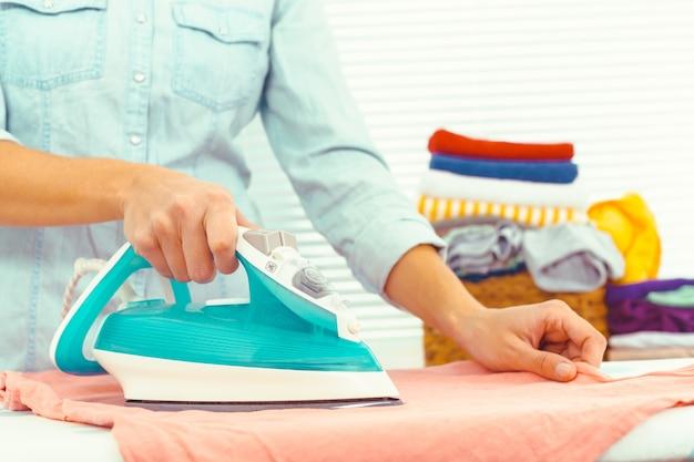 Closeup de mulher passando roupa na tábua