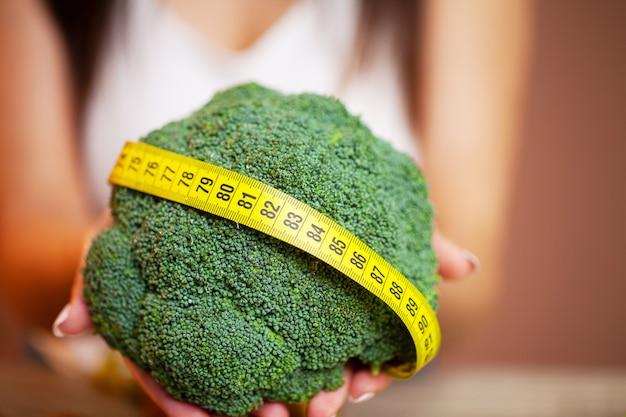 Closeup de mulher segurando brócolis com fita para medir
