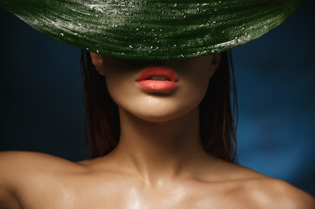 Closeup de mulher sem camisa com clavícula linda se escondendo atrás da folha.