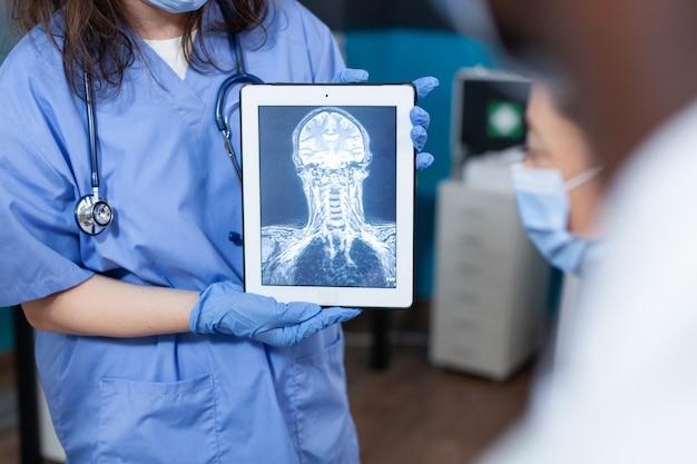 Closeup de mulher terapeuta assistente segurando computador tablet com radiografia