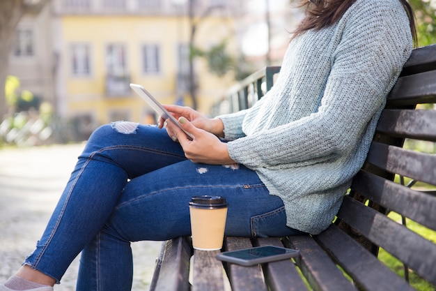 Closeup, de, mulher, usando, tabuleta, e, sentando, ligado, banco, ao ar livre