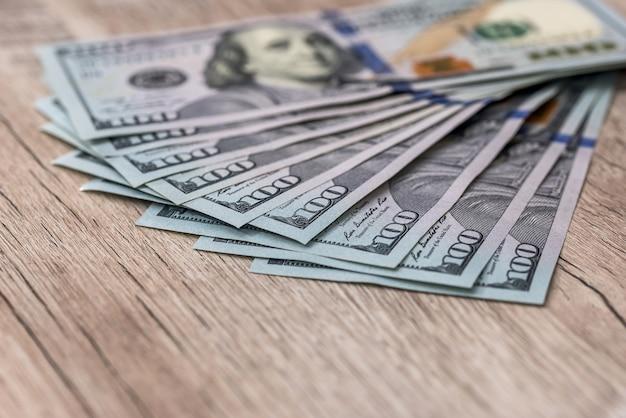 Closeup de notas de dólar americano em mesa de madeira