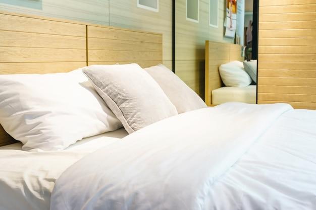 Closeup de novo conforto de cama com cabeceira de almofadas decorativas no quarto