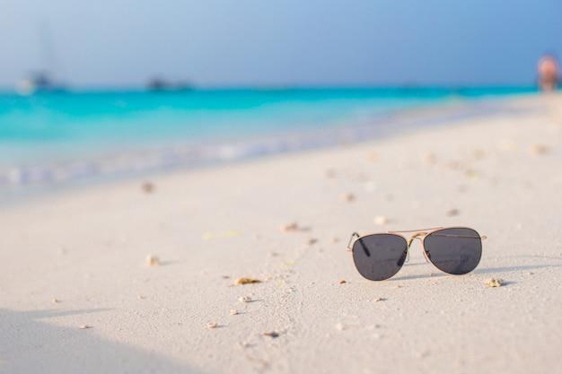 Closeup de óculos de sol na praia tropical