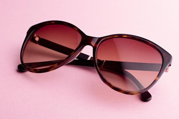 Closeup de óculos de sol tartaruga marrom superdimensionada oval clássico em fundo rosa, vista superior. tons retro modernos