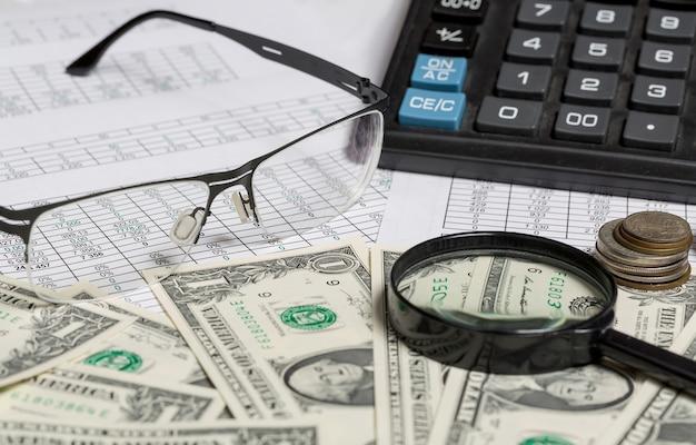 Closeup de óculos, notas de dólar e moedas em papel com dígitos