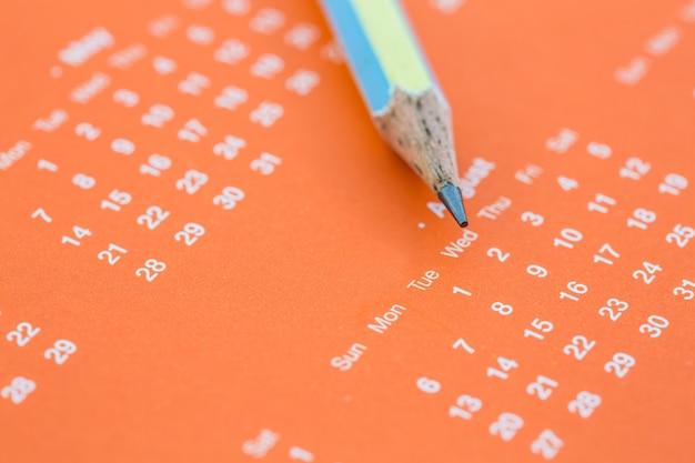 Closeup de página de calendário e lápis.