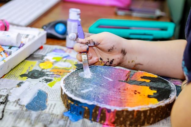 Closeup de paleta de madeira com tinta acrílica e pincel nas mãos do artista em madeira