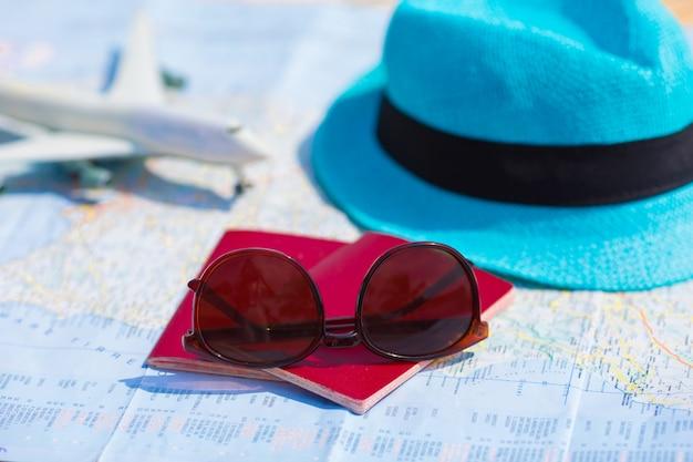 Closeup de passaportes, avião de brinquedo, óculos de sol no mapa