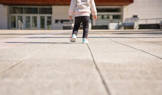 Closeup de pernas de menina com tênis e perneiras pretas, treinando ao ar livre
