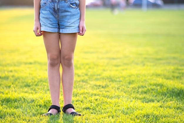 Closeup de pernas de menina criança em shorts jeans, em pé no gramado verde na noite quente de verão.