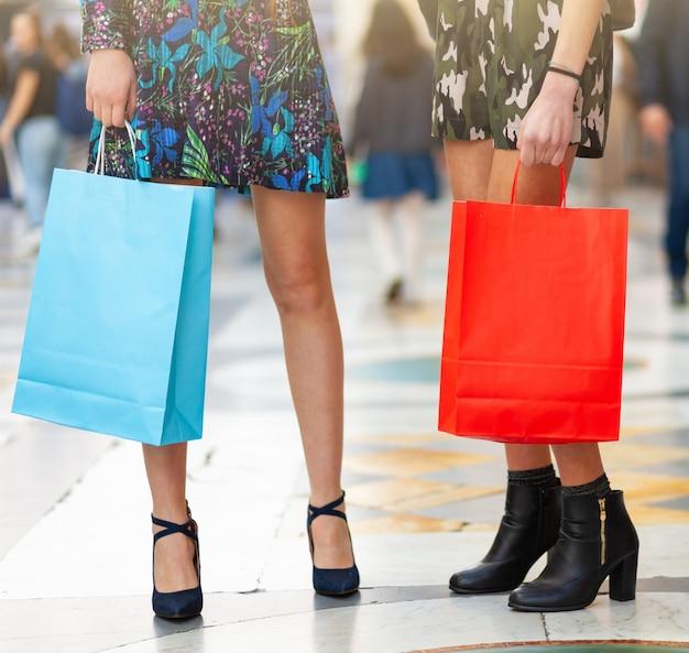 Closeup de pernas e sacolas de compras.