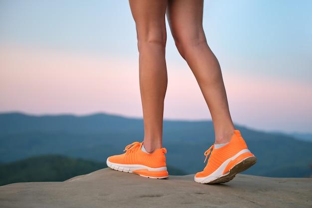 Closeup de pernas magras jovens femininas em sapatos de tênis laranja brilhante em pé na trilha de caminhada na montanha em noite de verão. estilo de vida ativo, corrida na natureza e exercício no conceito de ar fresco.