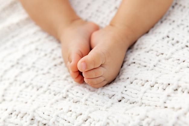 Closeup de pés de bebê adorável no cobertor de malha como pano de fundo em um foco seletivo, pernas infantis à luz natural