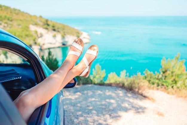 Closeup de pés de menina mostrando da janela do carro