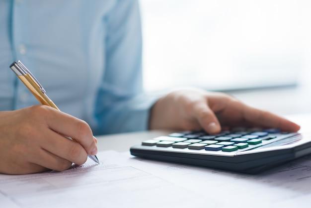 Closeup, de, pessoa, assinando, documento, e, usando, calculadora