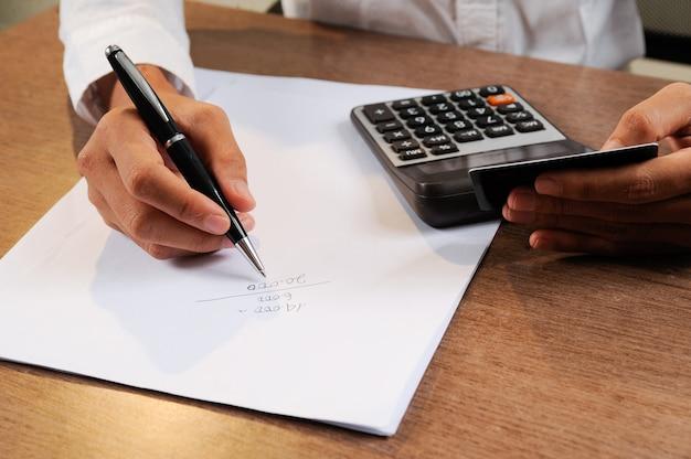 Closeup, de, pessoa, segurando, cartão crédito, e, calculando